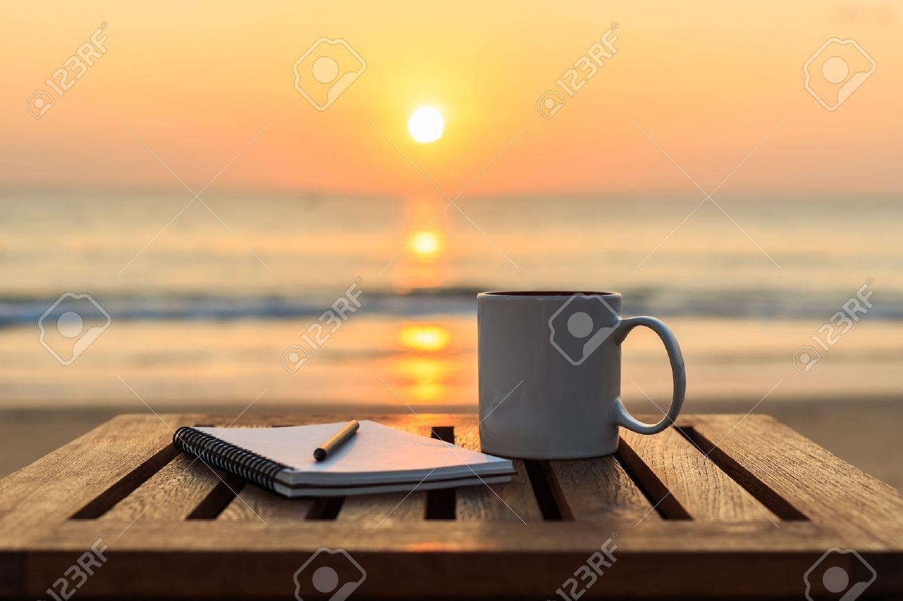 Close up coffee cup on wood table at sunset or sunrise beach Banque d'images - 47639945