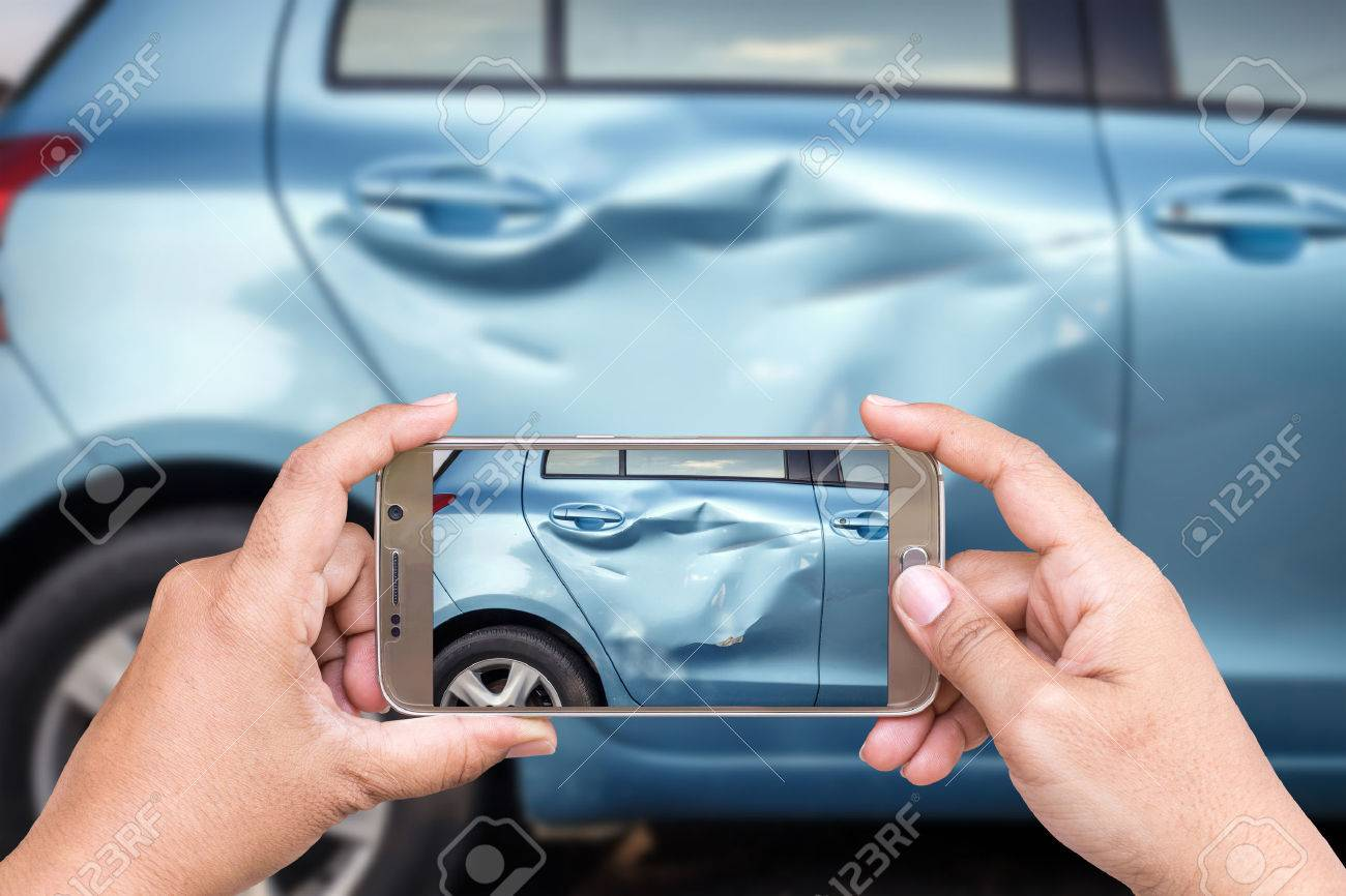 Close up hand of woman holding smartphone and take photo of car accident - 58203569