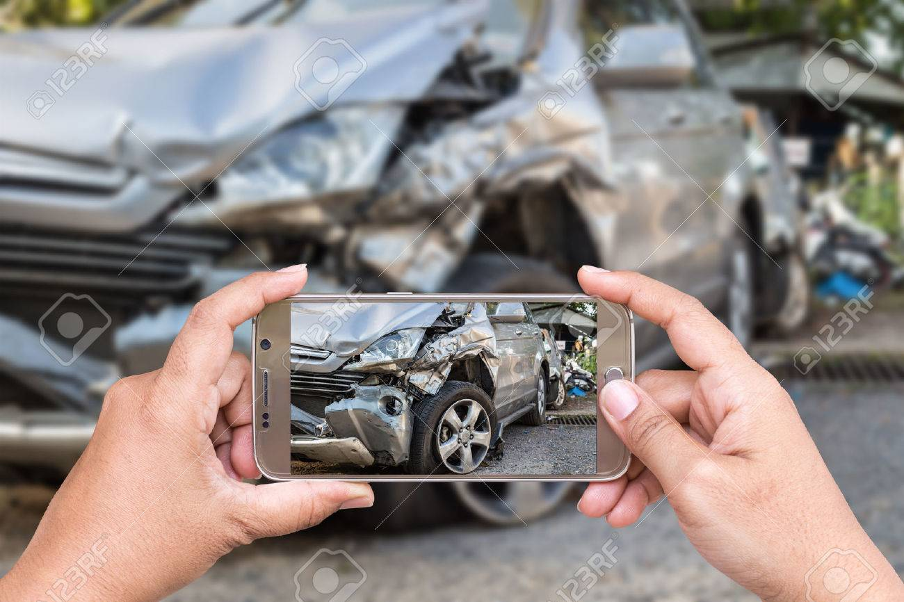 Close up hand of woman holding smartphone and take photo of car accident Banque d'images - 58205947