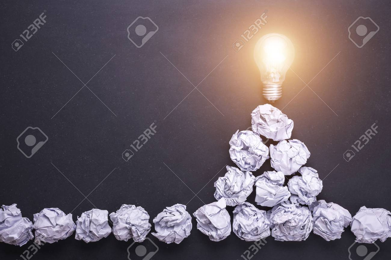 Top view crumpled white paper and light bulbs on black stone board. Create idea concept - 88366821