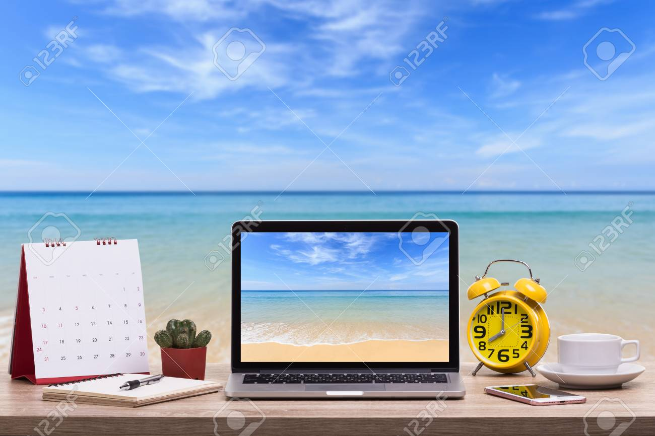 Modern laptop computer, Coffee cup, alarm clock, notebook and calendar on wooden table and view of tropical beach background. - 97014015