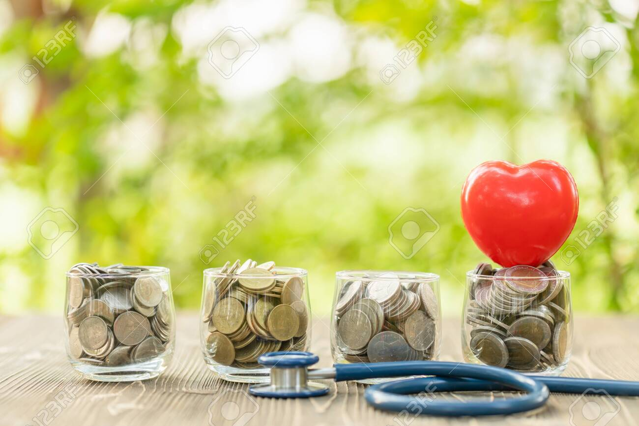 Close up blue stethoscope and jar of coin on wooden table. - 141526826