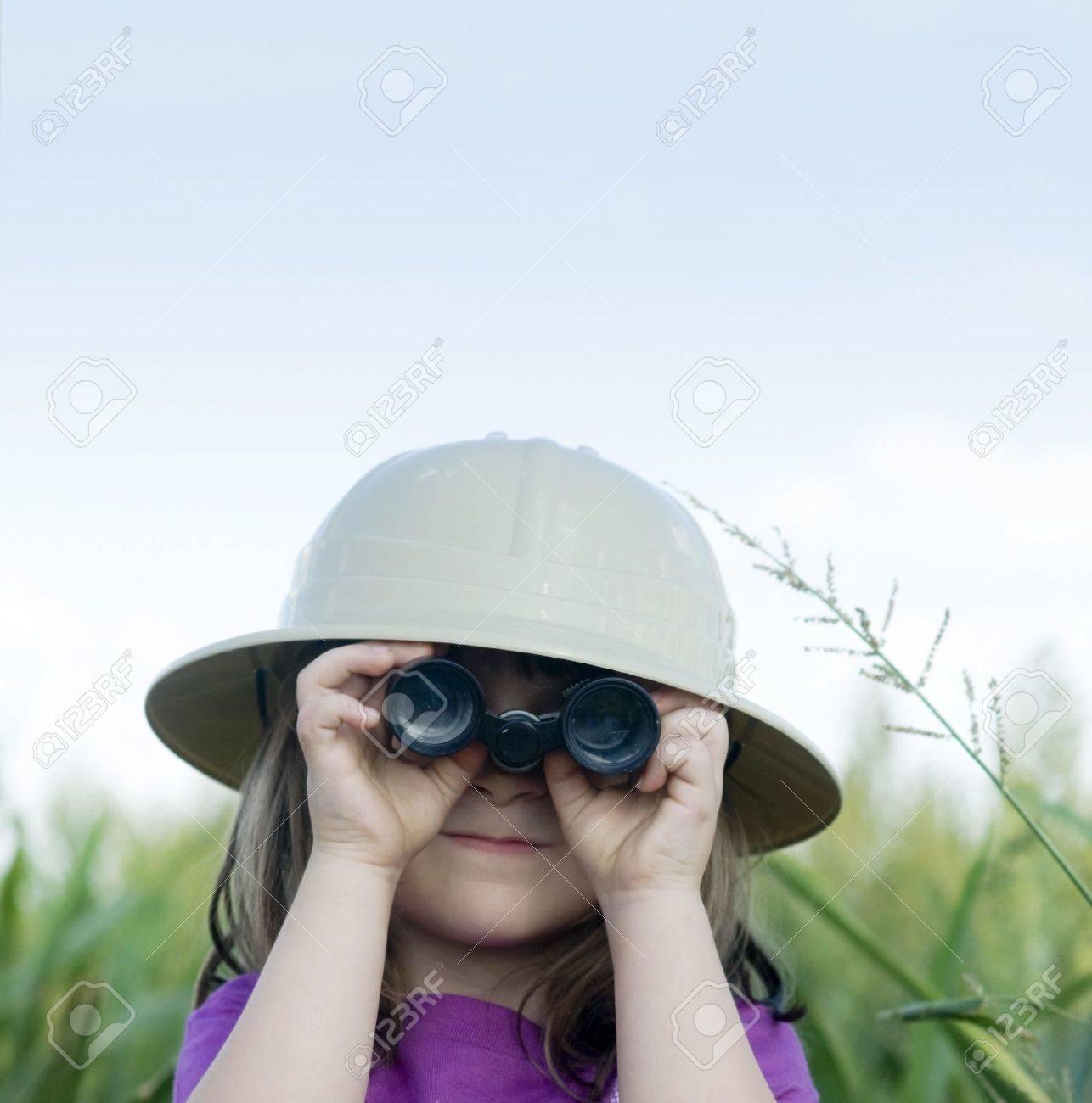 f4f0dc28e968e Little girl looking through binoculars with safari hat Stock Photo - 3599519