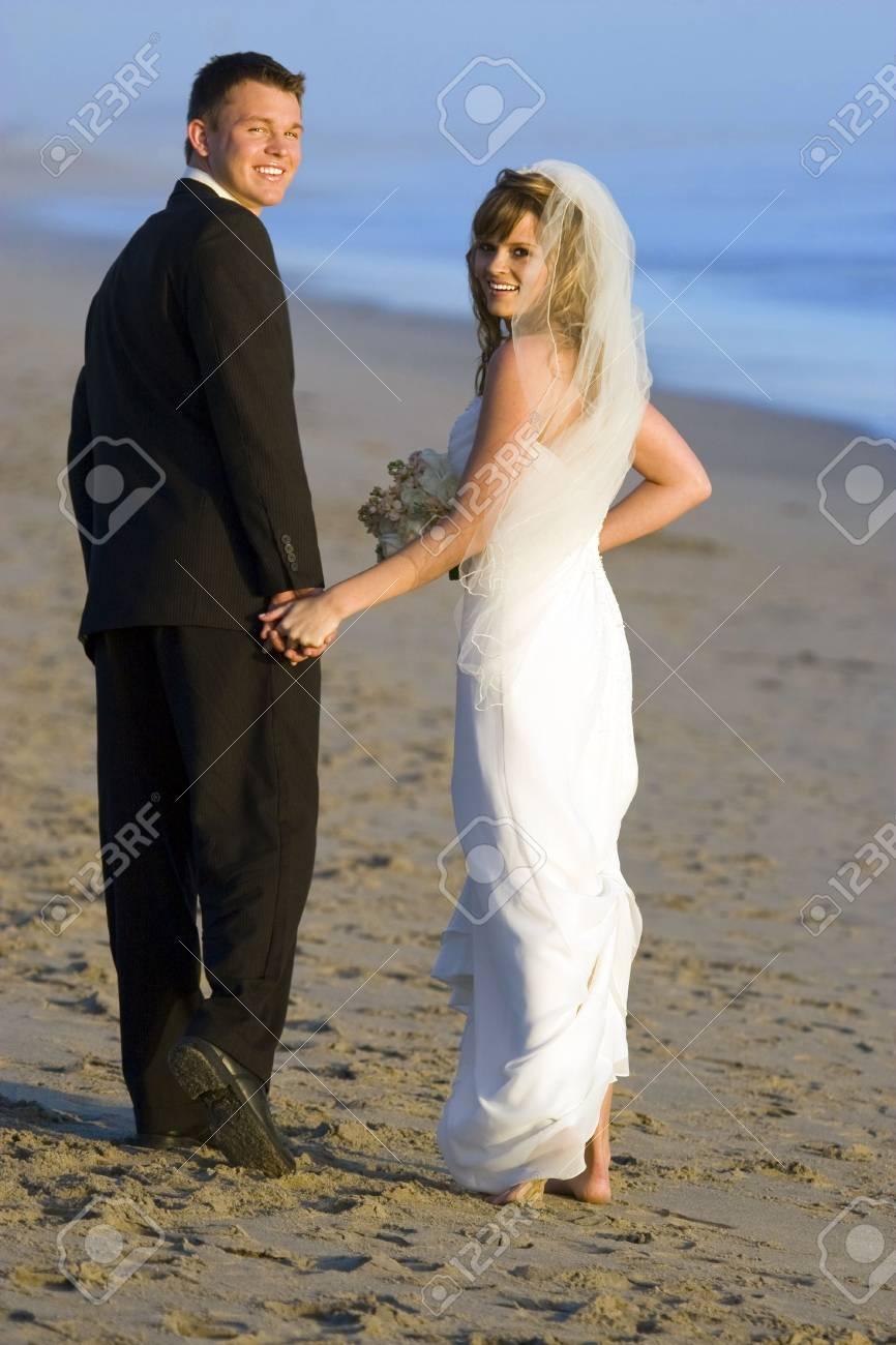 Loving wedding couple walking on the beach Stock Photo - 4874436