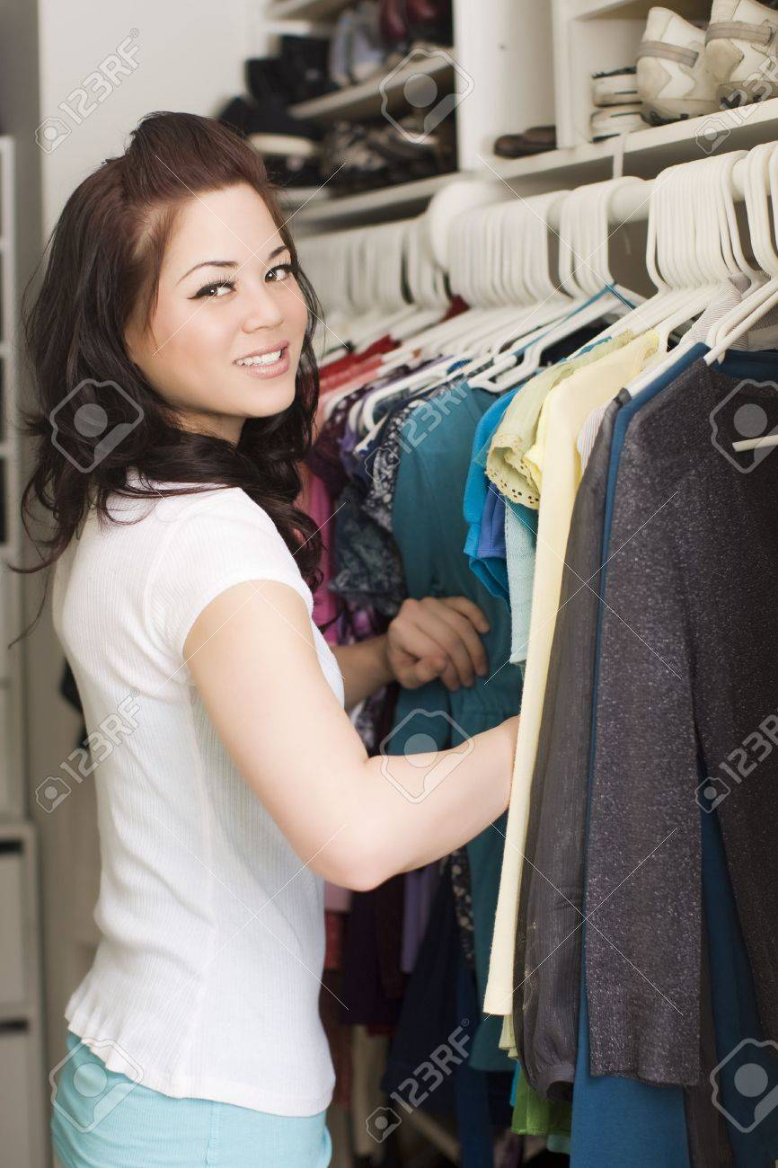 Woman looking at clothes in a closet - 4949842