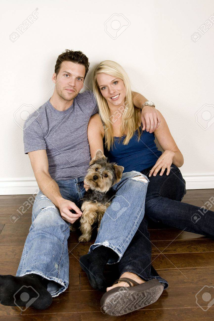 Attractive young couple sitting in their new home with their dog - 5065288