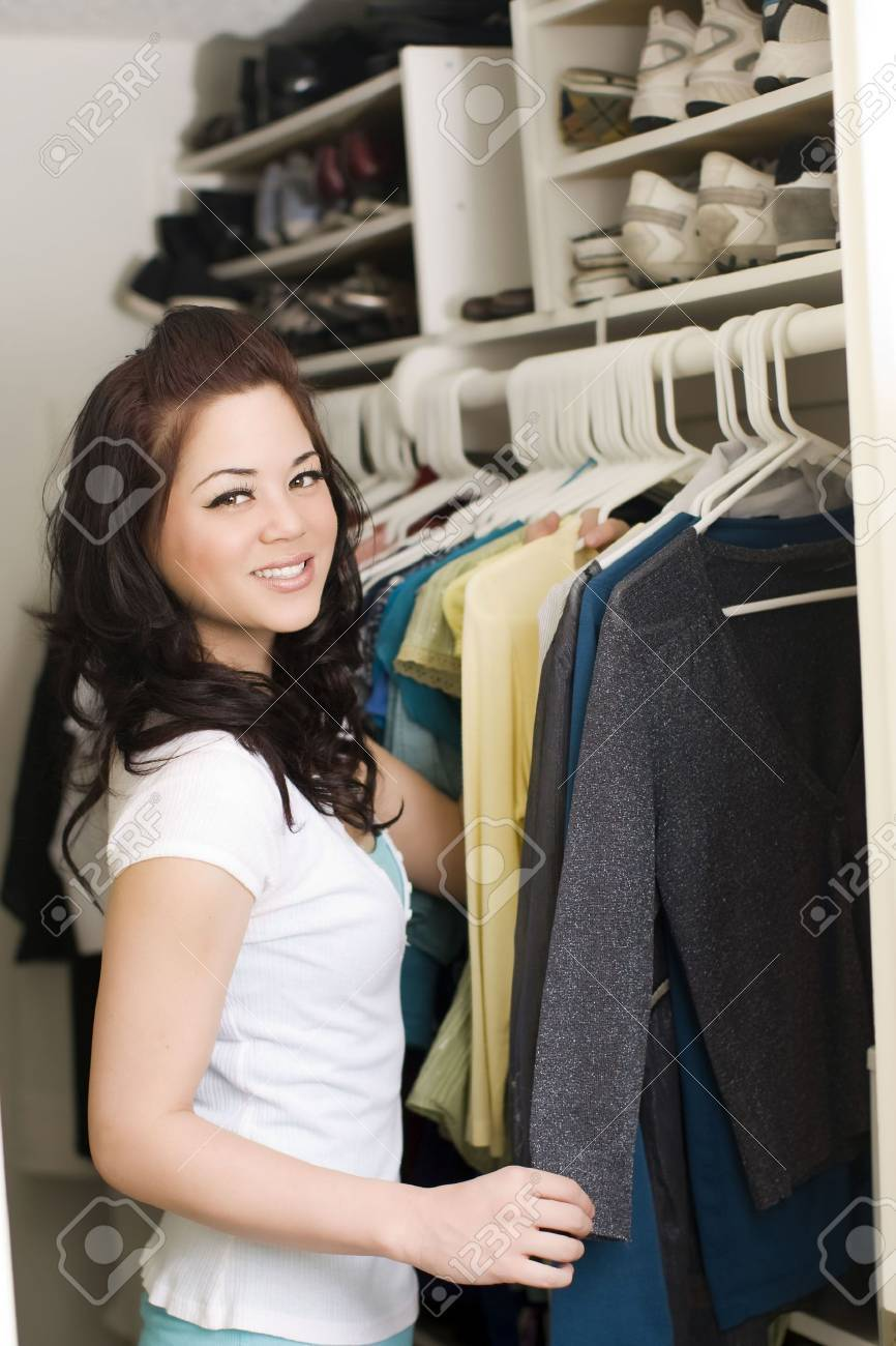 Woman looking at clothes in a closet - 5154378