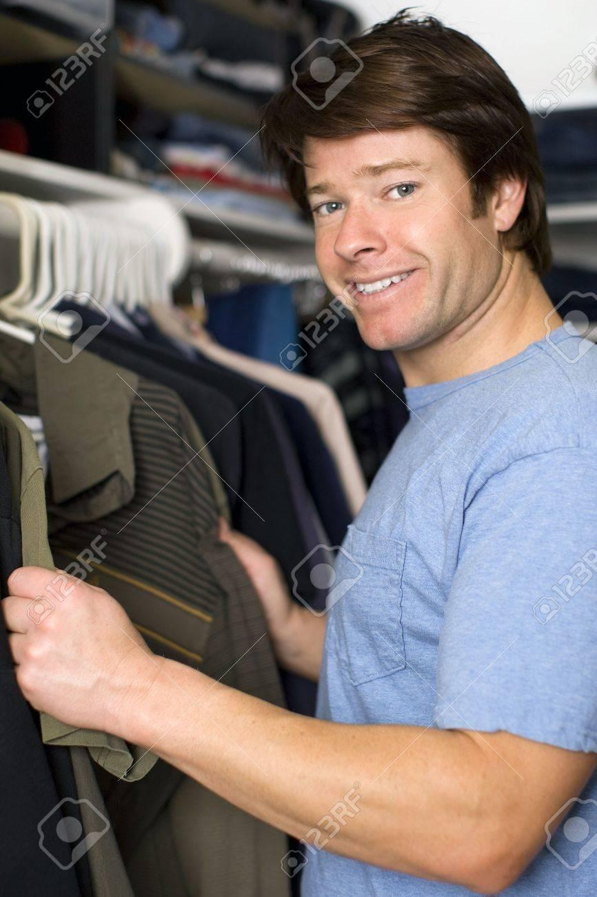 Man looking through shirts in his closet Stock Photo - 5372504