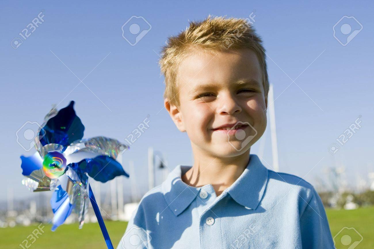 Little boy blowing on a pinwheel - 5447276