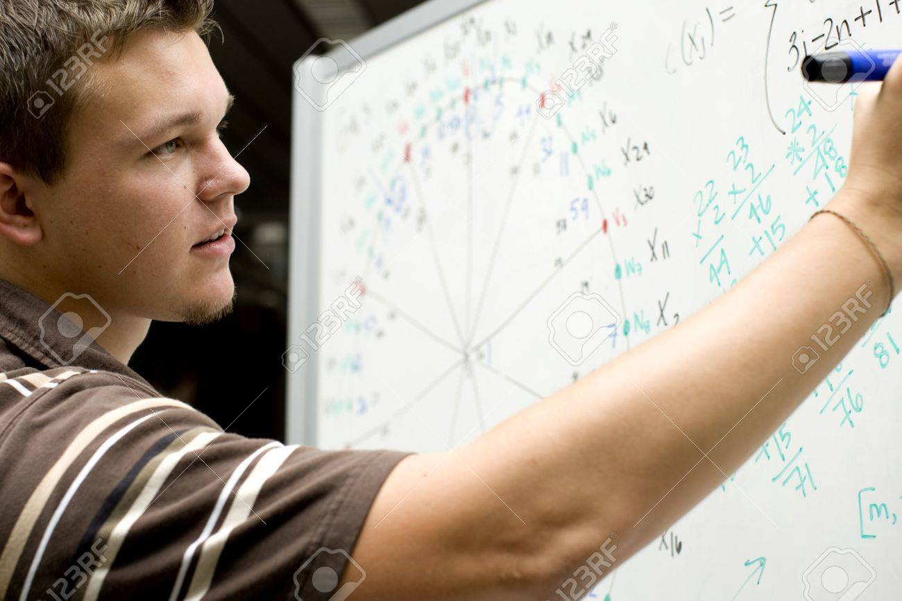Young man at school doing a math equation - 5454964