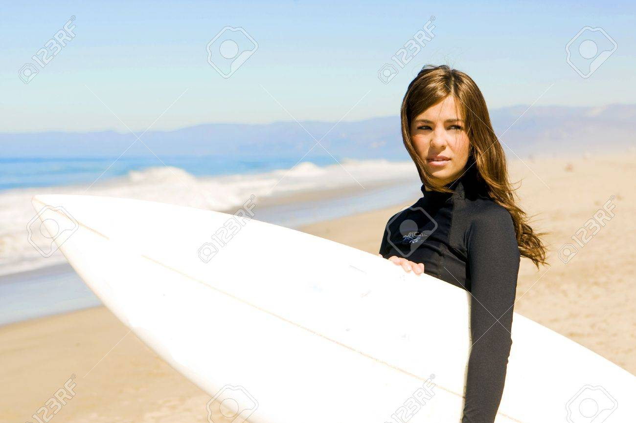 Beautiful young woman at the beach with surfboard - 5534628