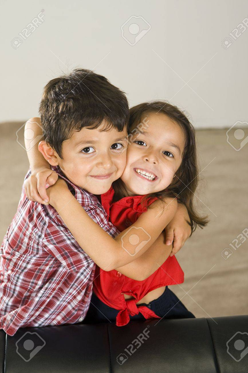 Cute brother and sister sitting on a couch - 5679726