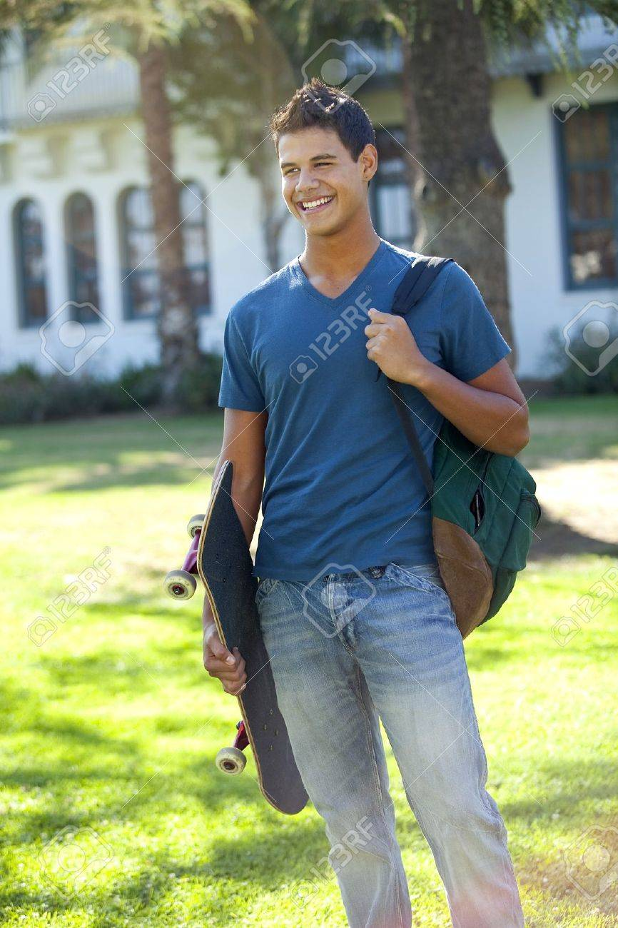 Student with skateboard and backpack outside school - 8671702