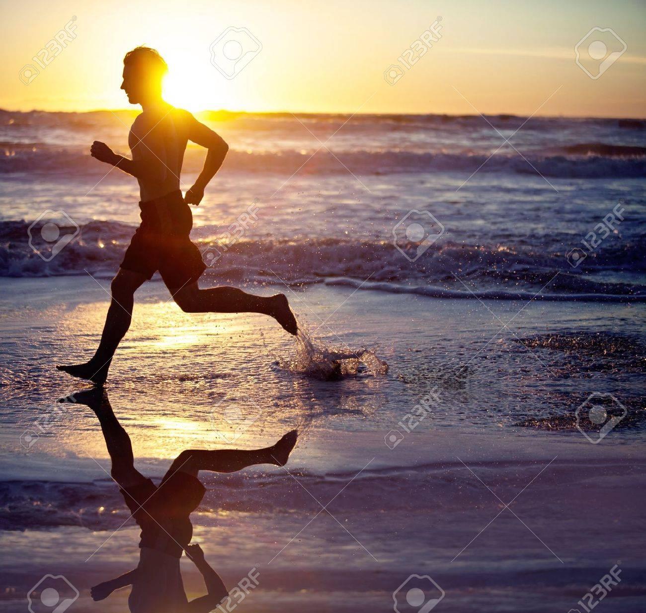 Man running on the beach at sunset - 18304534