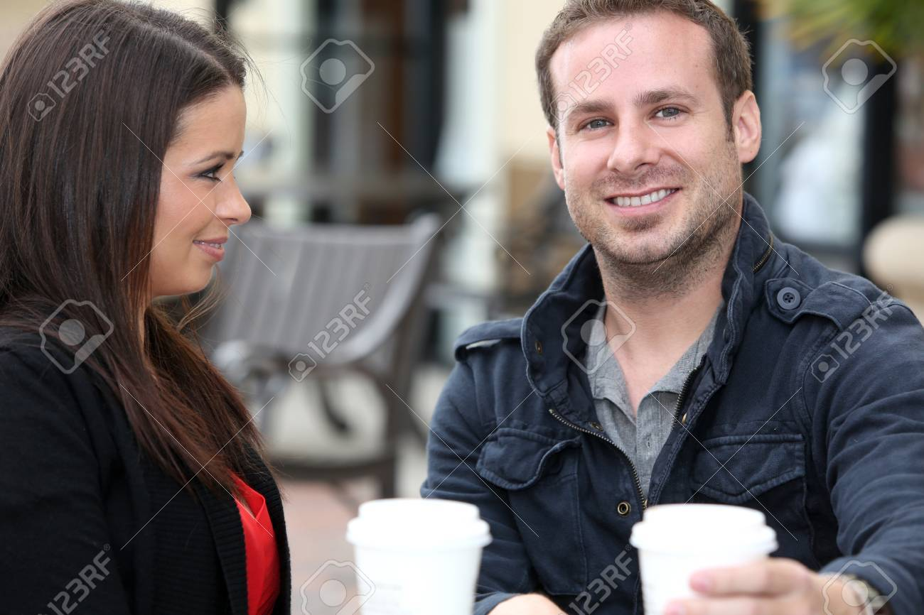 Young couple drinking coffee outside - 18304531