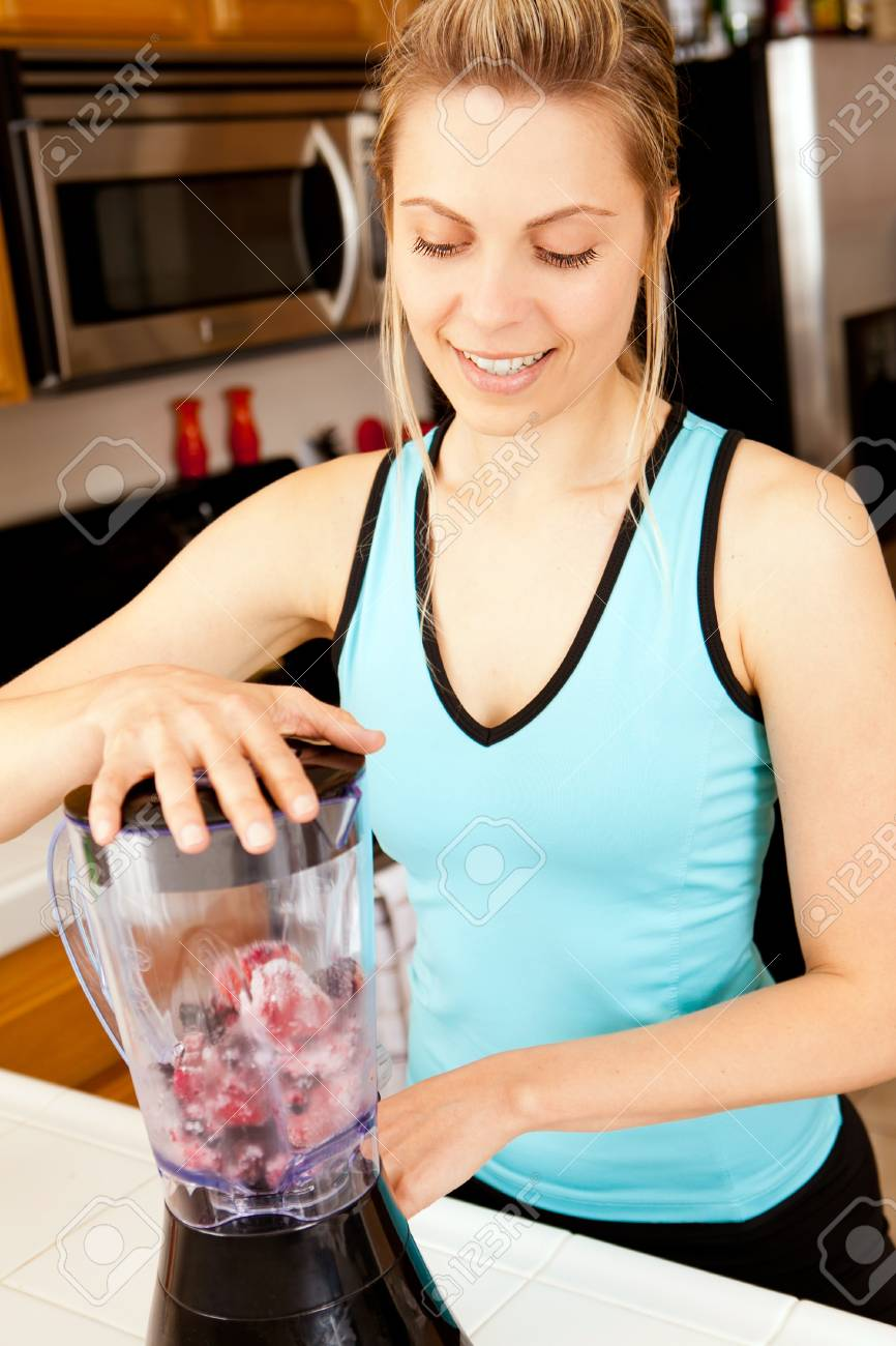 Young woman with a blender filled with berries - 18304143