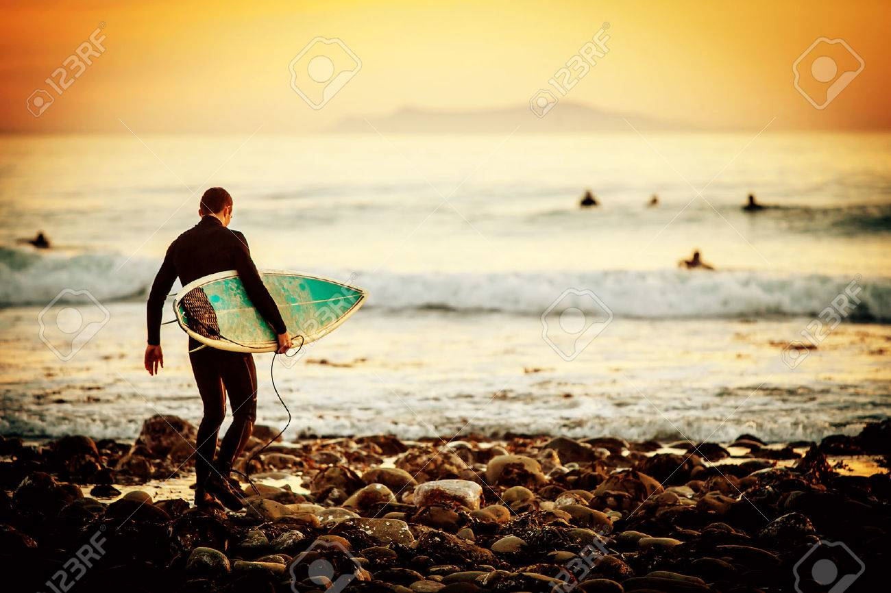 Surfer on the beach at sunset - 31811300
