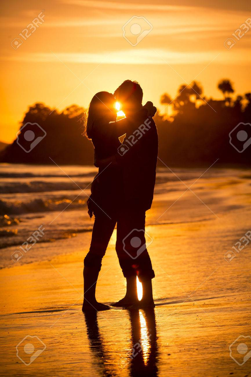 Silhouette of a couple on the beach at sunset - 31905118