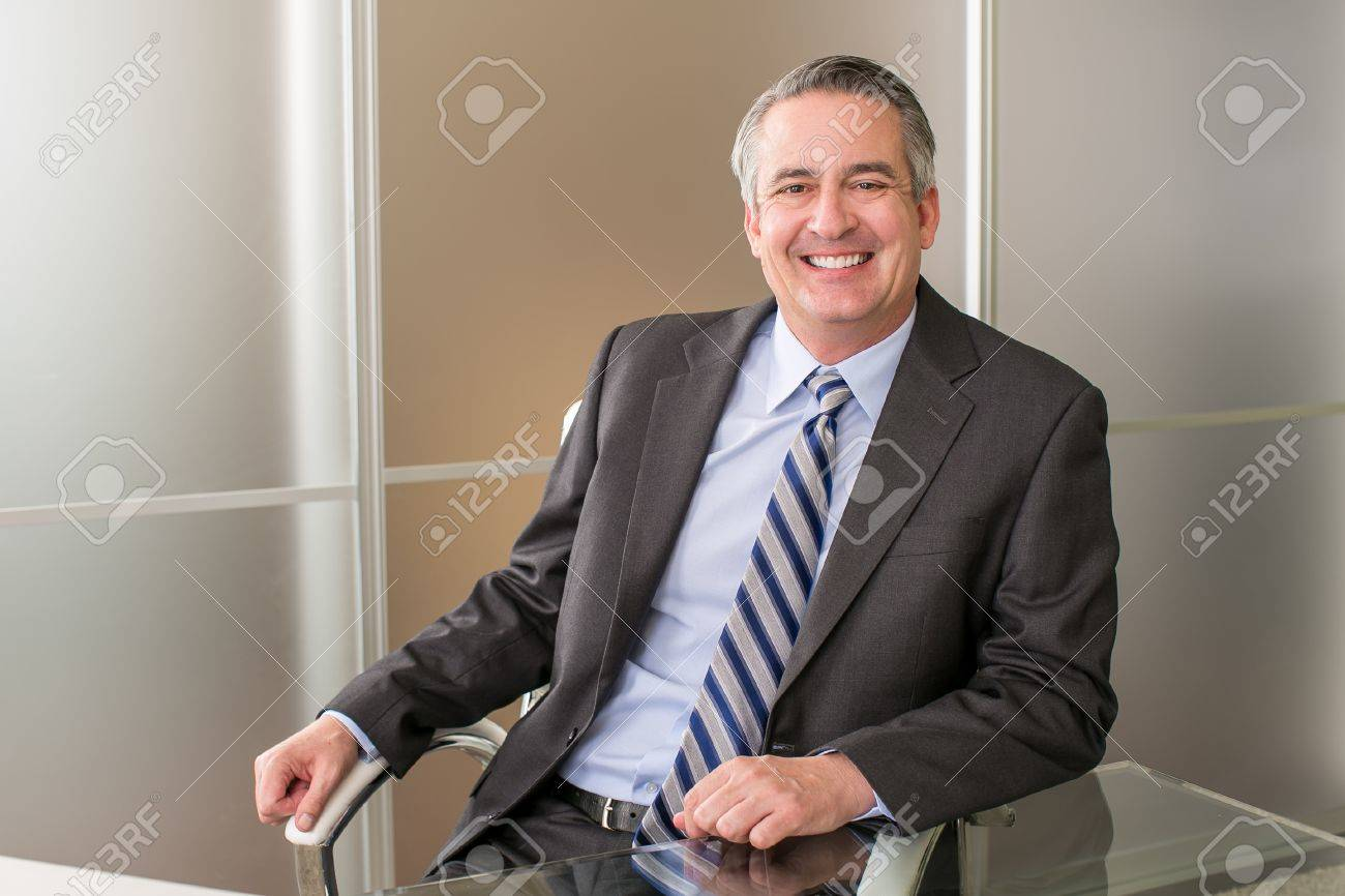 Mature happy smiling business man in an office - 46943334