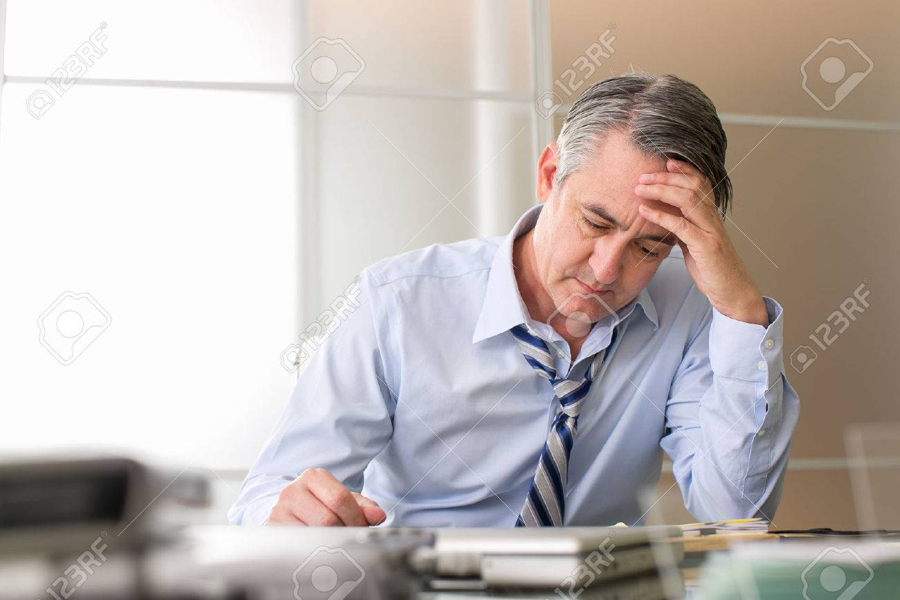 Frustrated stressed business man in an office - 50080510