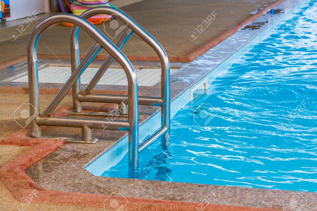 Angle of clean water in a blue swimming pool, pool ladders.
