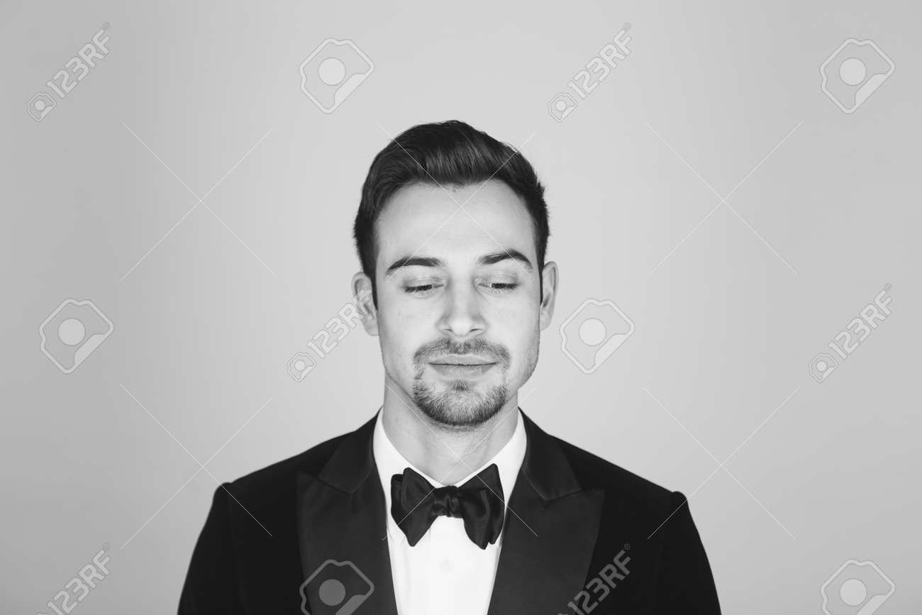 Studio portrait of a young caucasian man in a tuxedo, upset, looking down, against plain studio background - 158227699