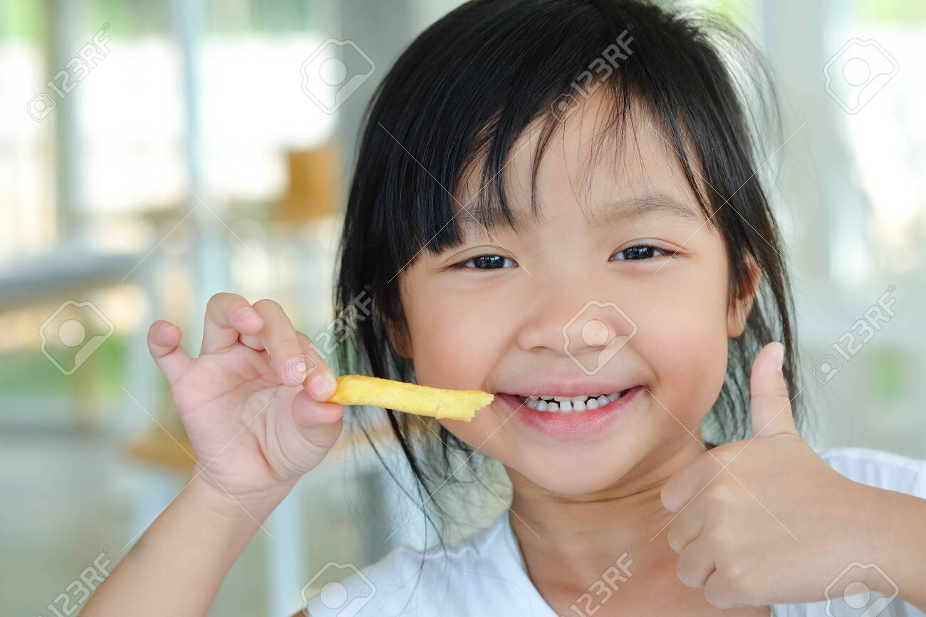 Asian child girl show thumb up and happy eating french fries - 150603681