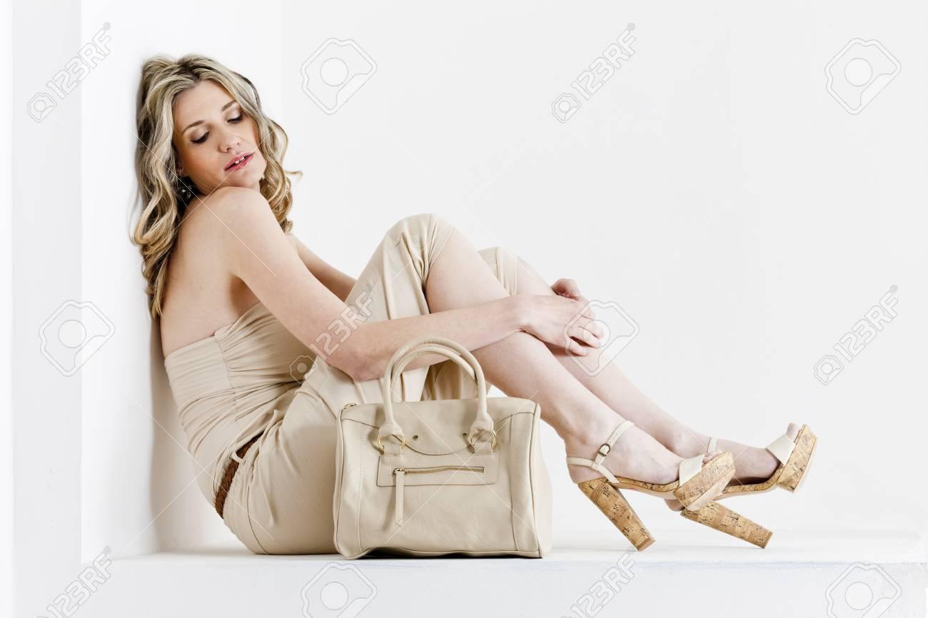 f26cb154de7d Archivio Fotografico - Donna seduta indossa abiti estivi e scarpe con una  borsetta