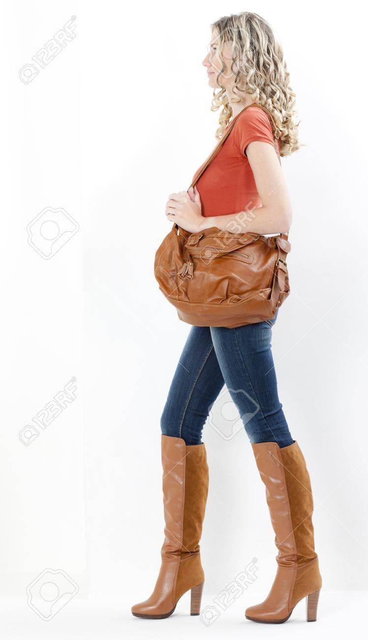 Mode femme portant des bottes brunes avec un sac à main