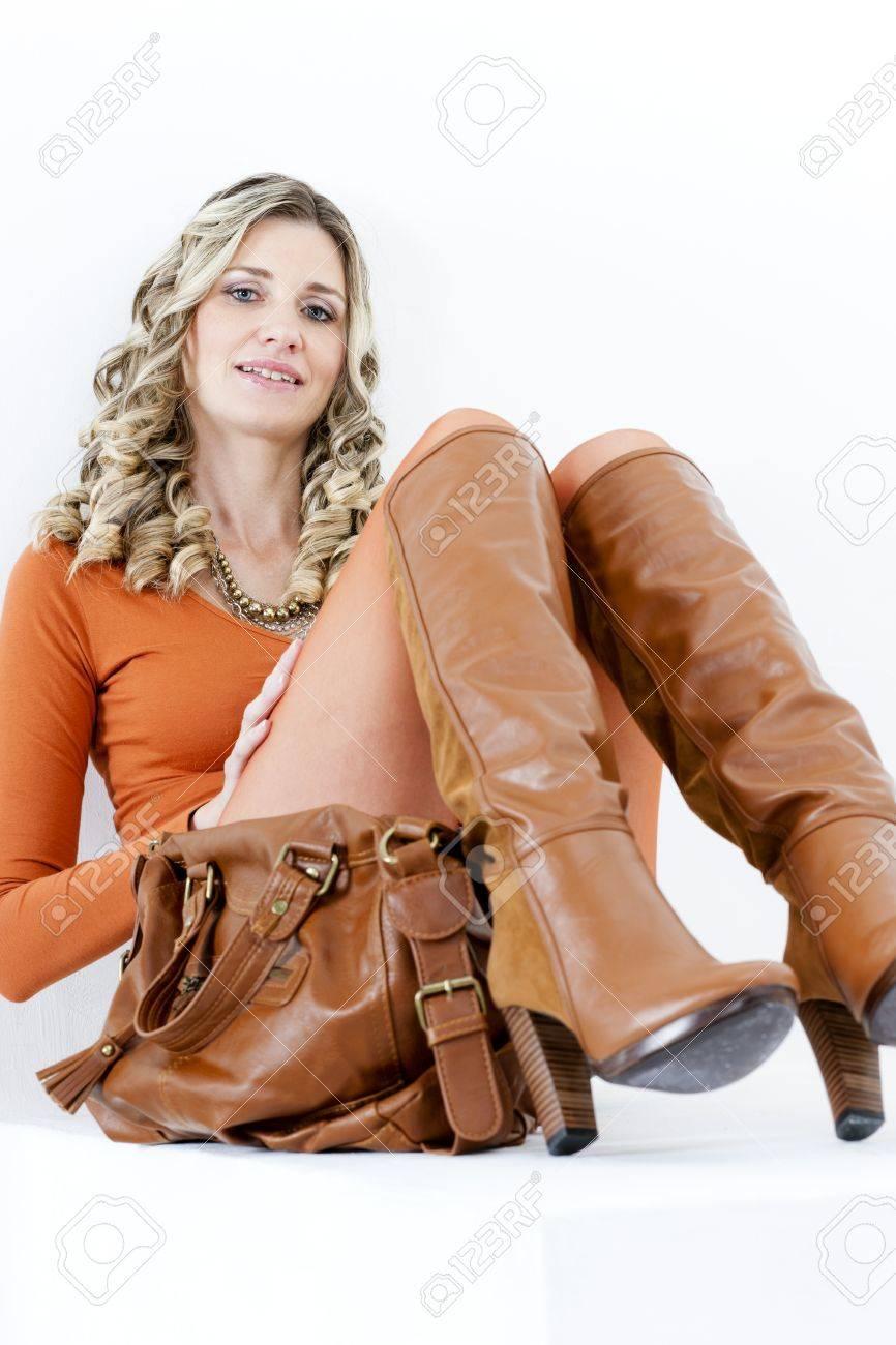 Portrait de femme assise portant la mode des bottes brunes avec un sac à main