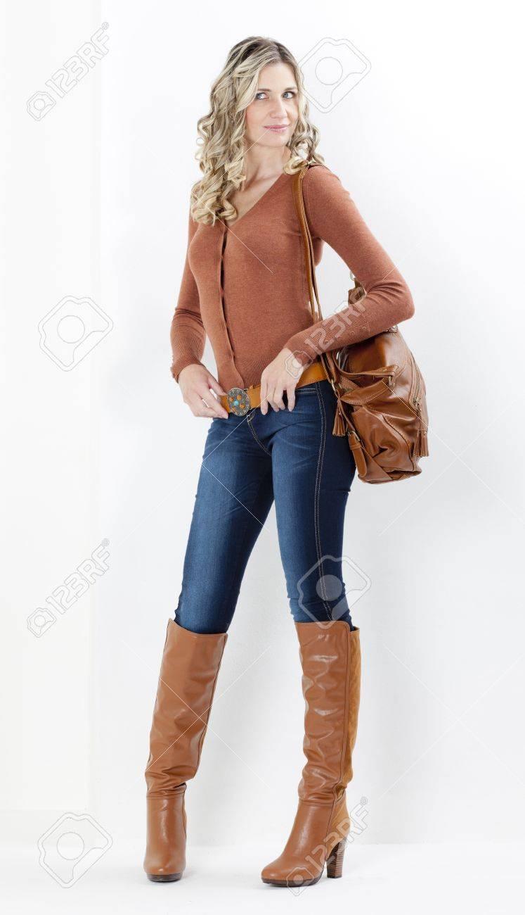 Femme debout portant la mode des bottes brunes avec un sac à main