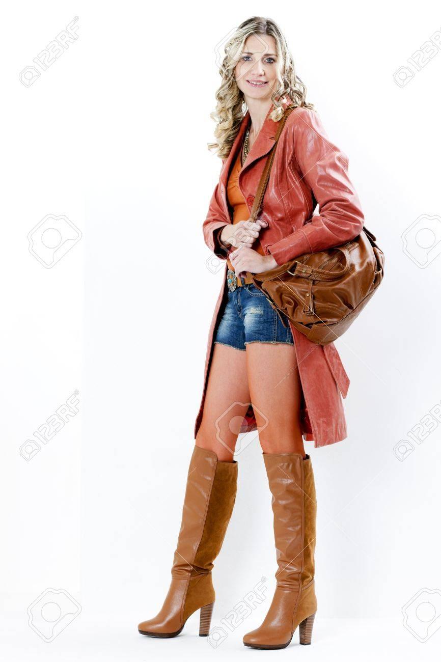 Femme, debout, portant à la mode des bottes brunes avec un sac à main