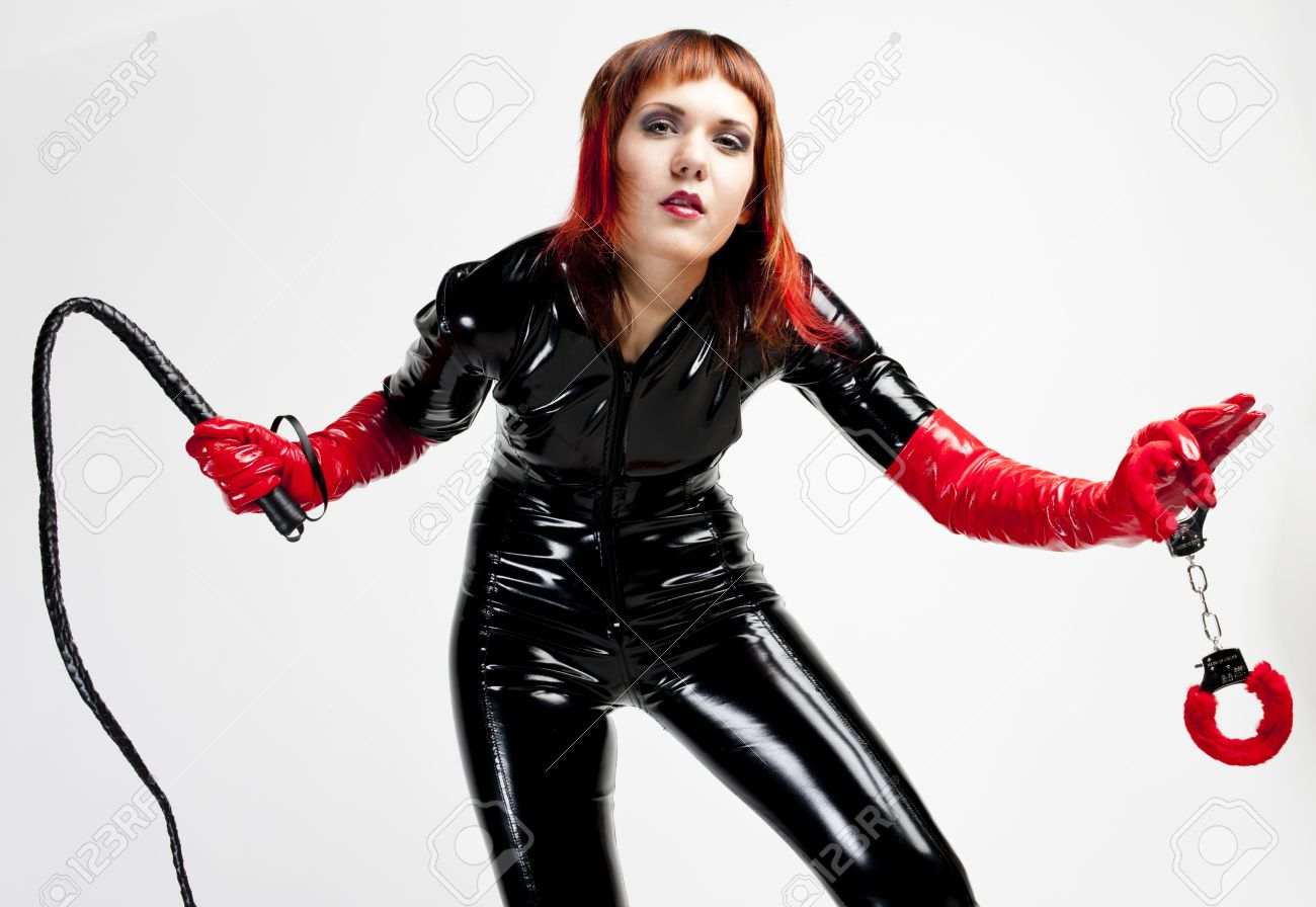 standing woman wearing extravagant clothes holding a whip and handcuffs Stock Photo - 13679318
