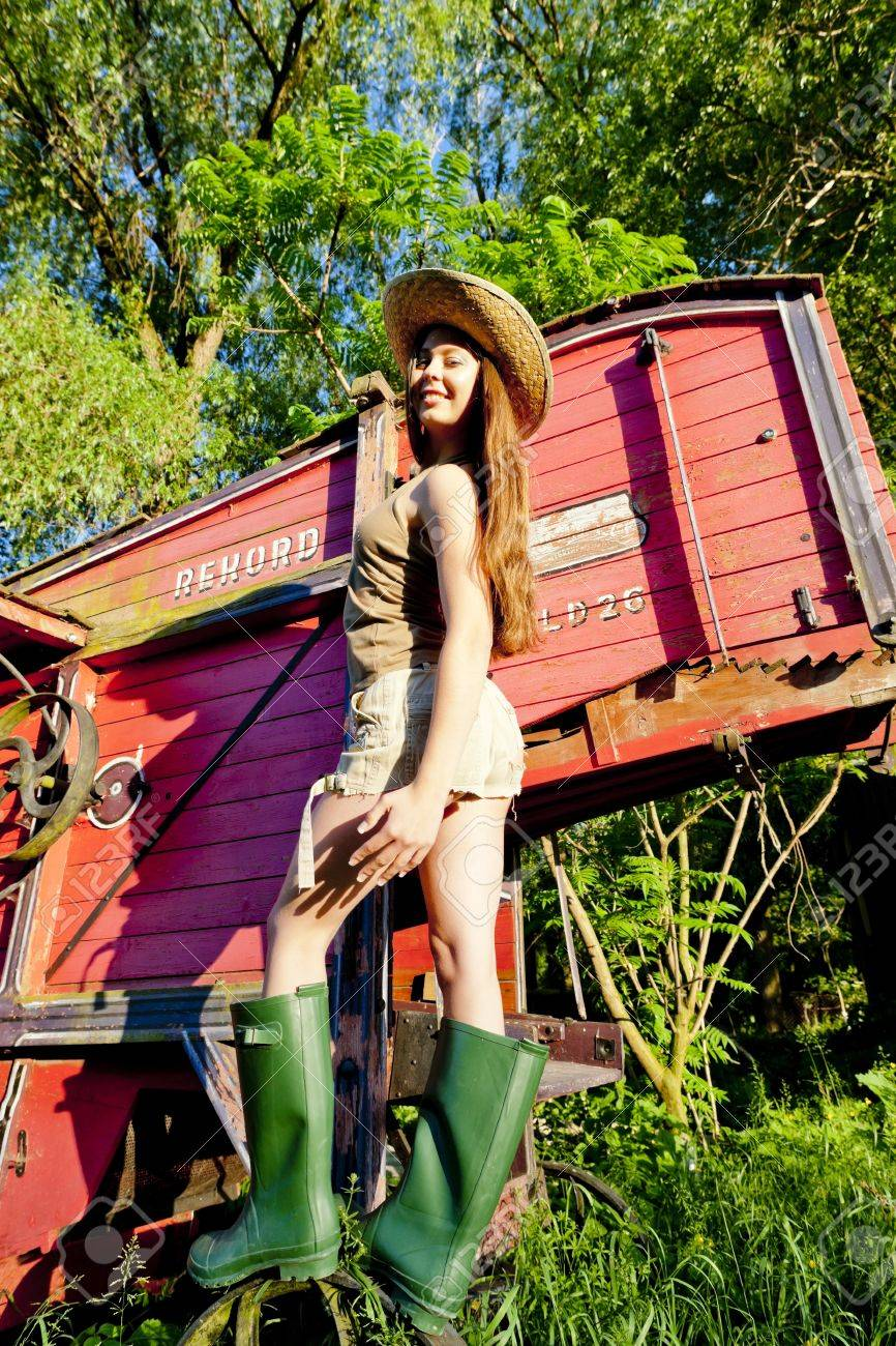 young woman standing by old threshing machine Stock Photo - 17718059