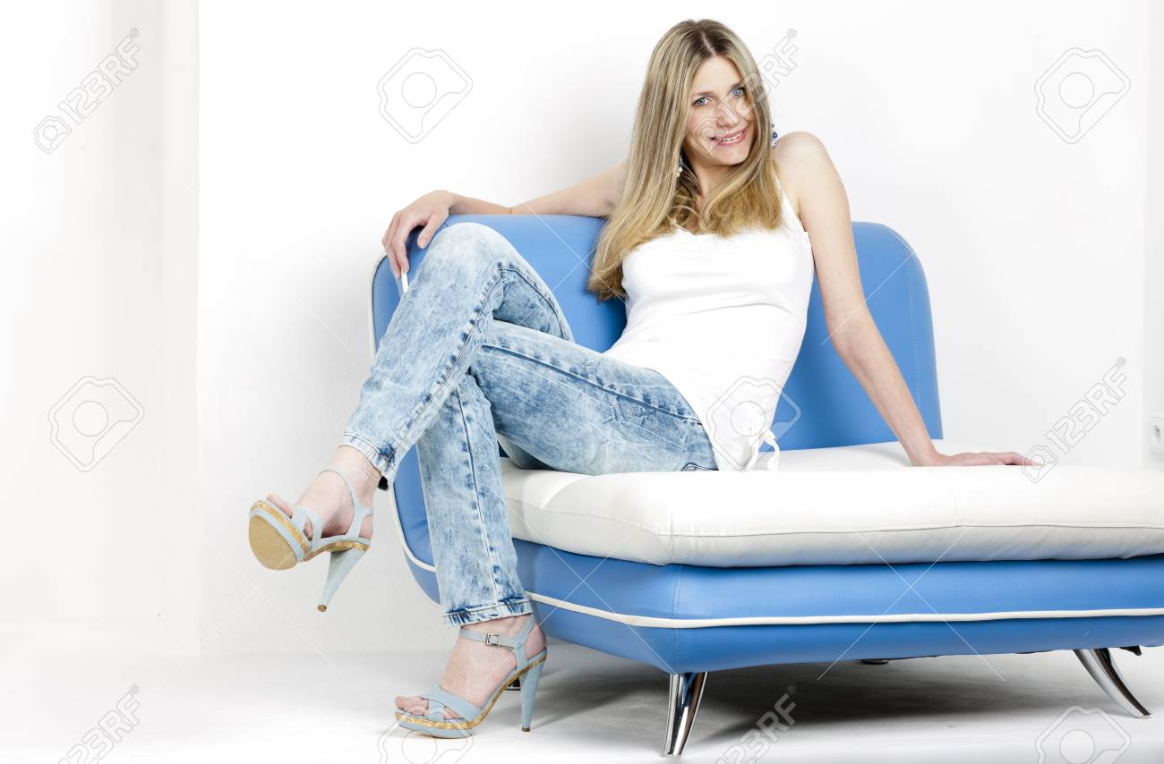 woman sitting on sofa wearing jeans and summer shoes Stock Photo - 18604259