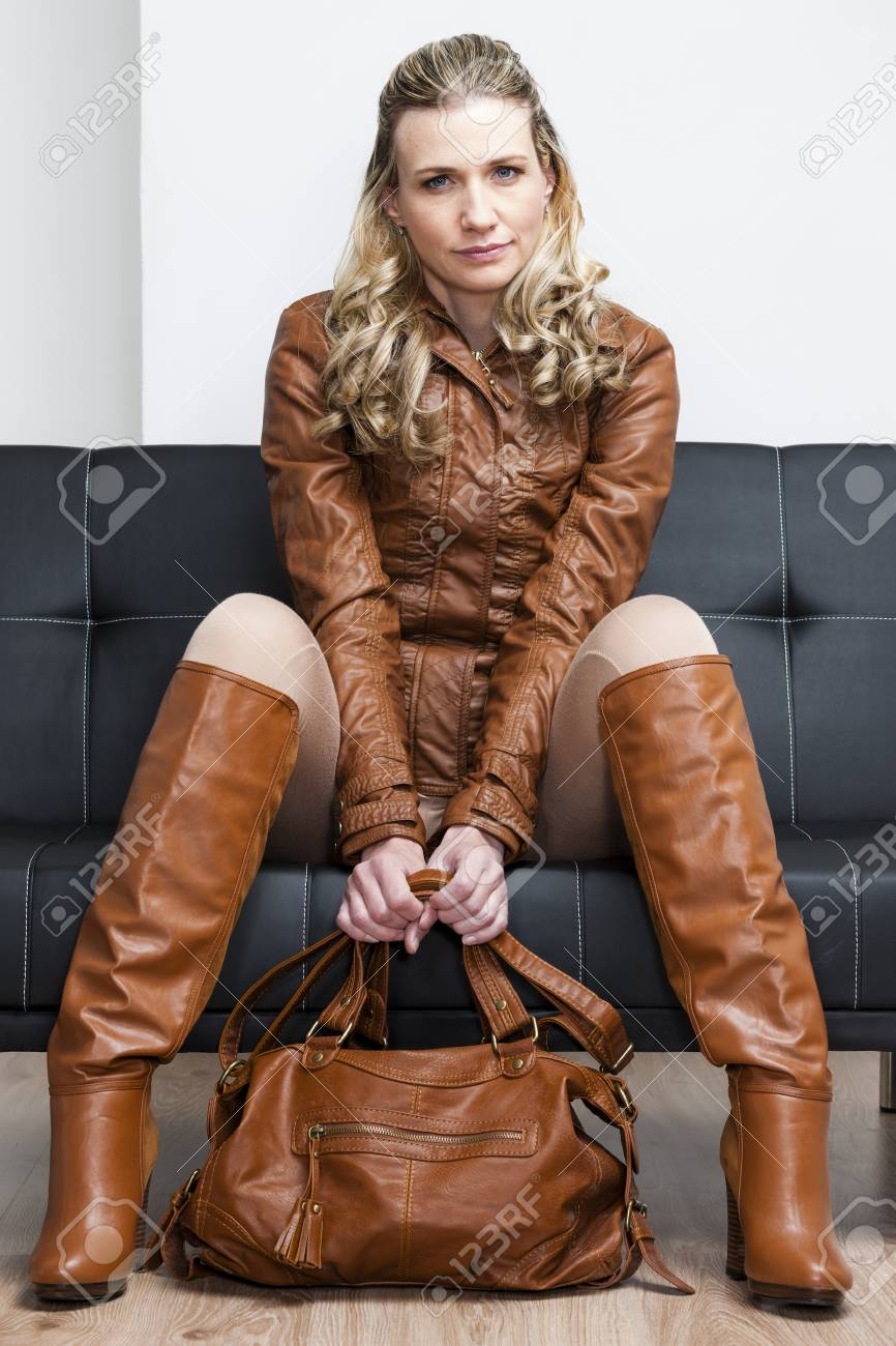 Woman Wearing Brown Jacket And Boots Sitting On Sofa Stock Photo