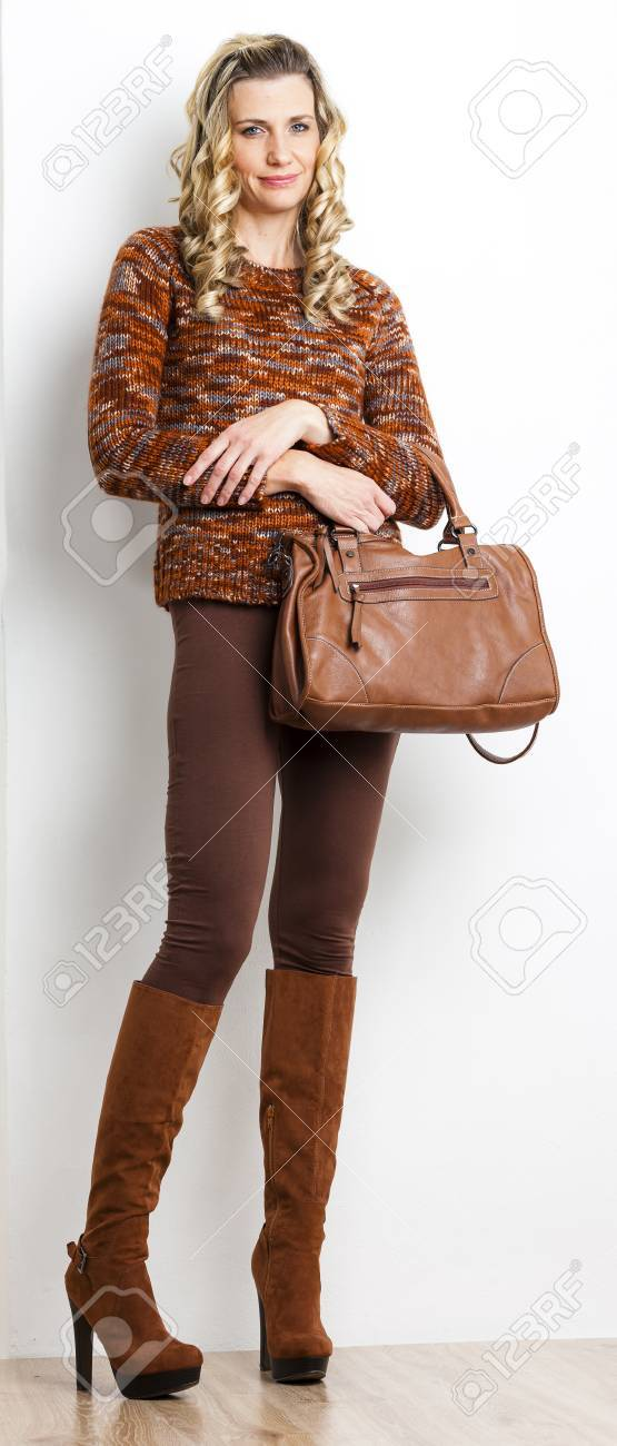 Femme debout portant des vêtements et des bottes brunes avec un sac à main