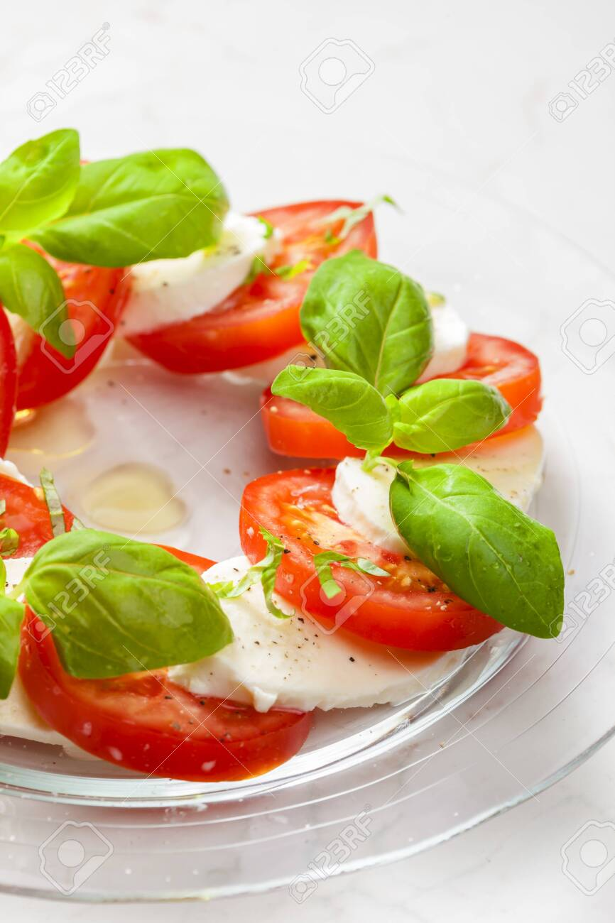 Delicious caprese salad with ripe tomatoes and mozzarella cheese with fresh basil leaves. Italian food - 138041644