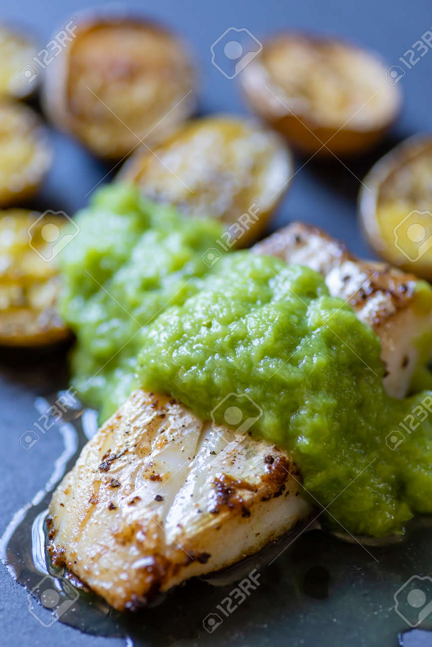 frilled cod fish with green asparagus sauce and fried potatoes - 169976086