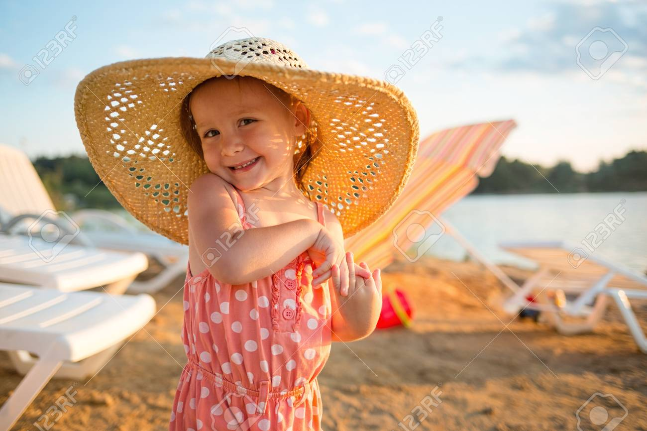 5bb261564bb6f baby on the beach.girl Flirty in the hat on the background of sun loungers