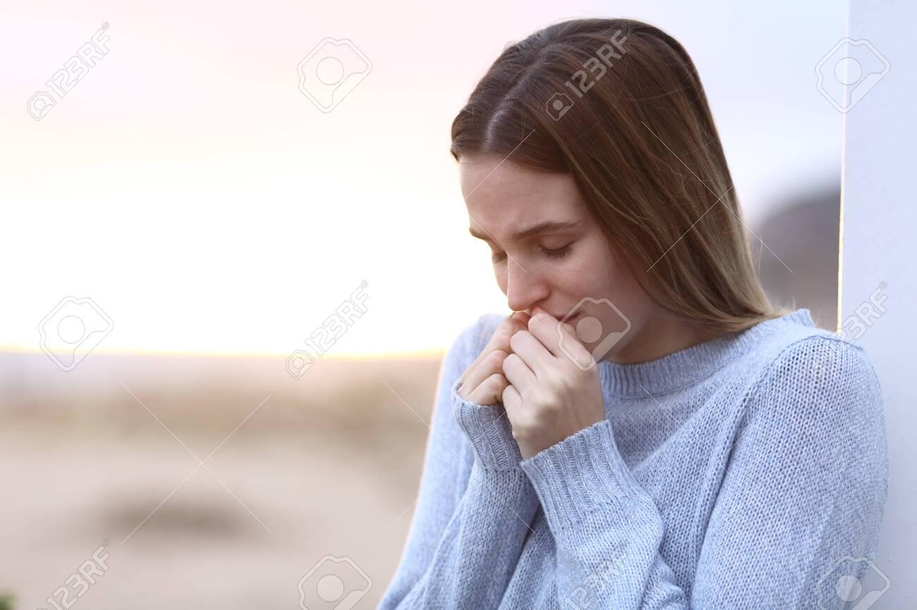 Sad girl complaining alone standing on the beach - 139901256