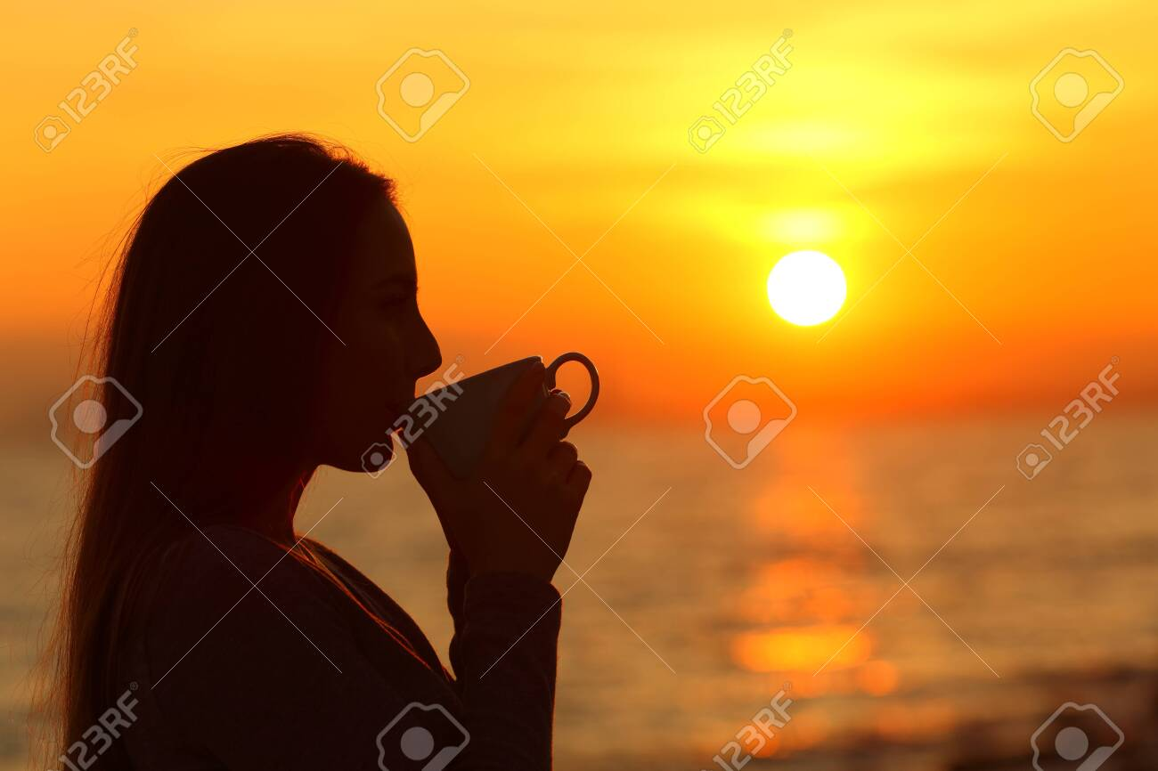 Side view portrait od a woman silhouette drinking coffee at sunrise on the beach - 139886742