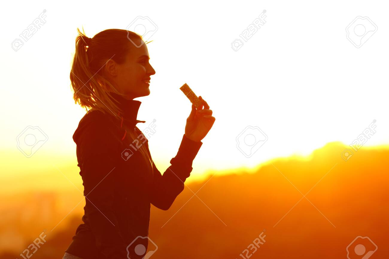 Silhouette of runner woman eating energy bar after running at sunset in the mountain - 140301623
