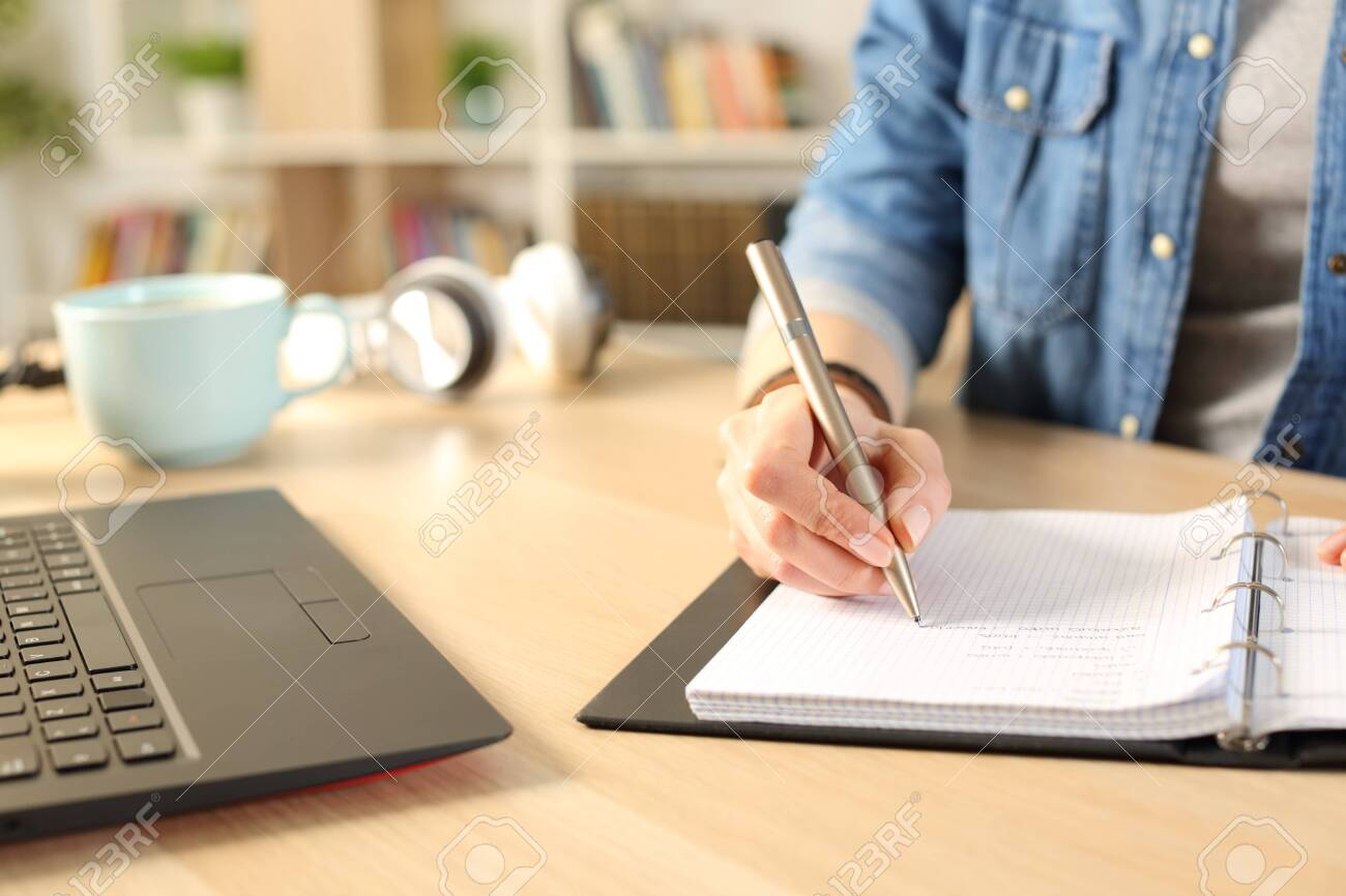 Close up of student girl hands writing on notebook on a desk at home - 147153994
