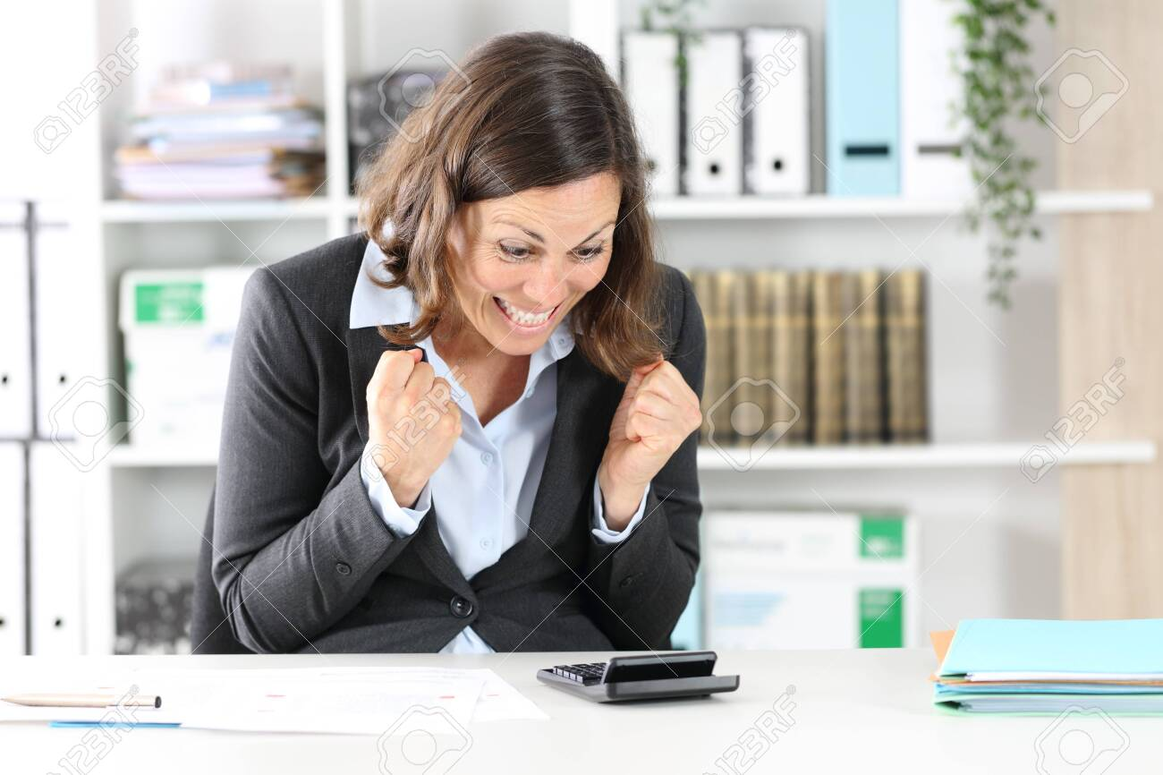Excited adult executive woman celebrating checking result on calculator sitting on a desk at office - 148254497