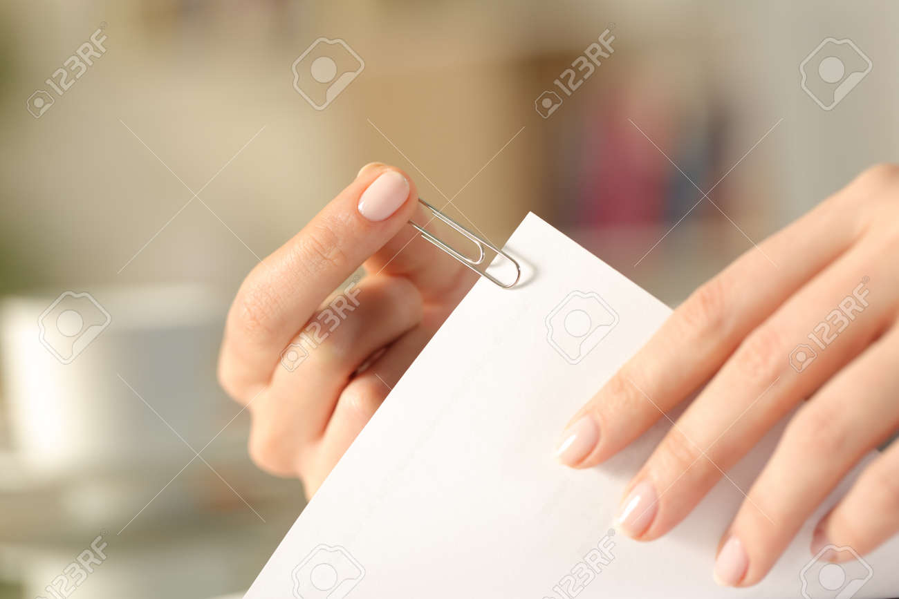 Close up of a woman hands putting a paper clip on a sheet at home - 156466050