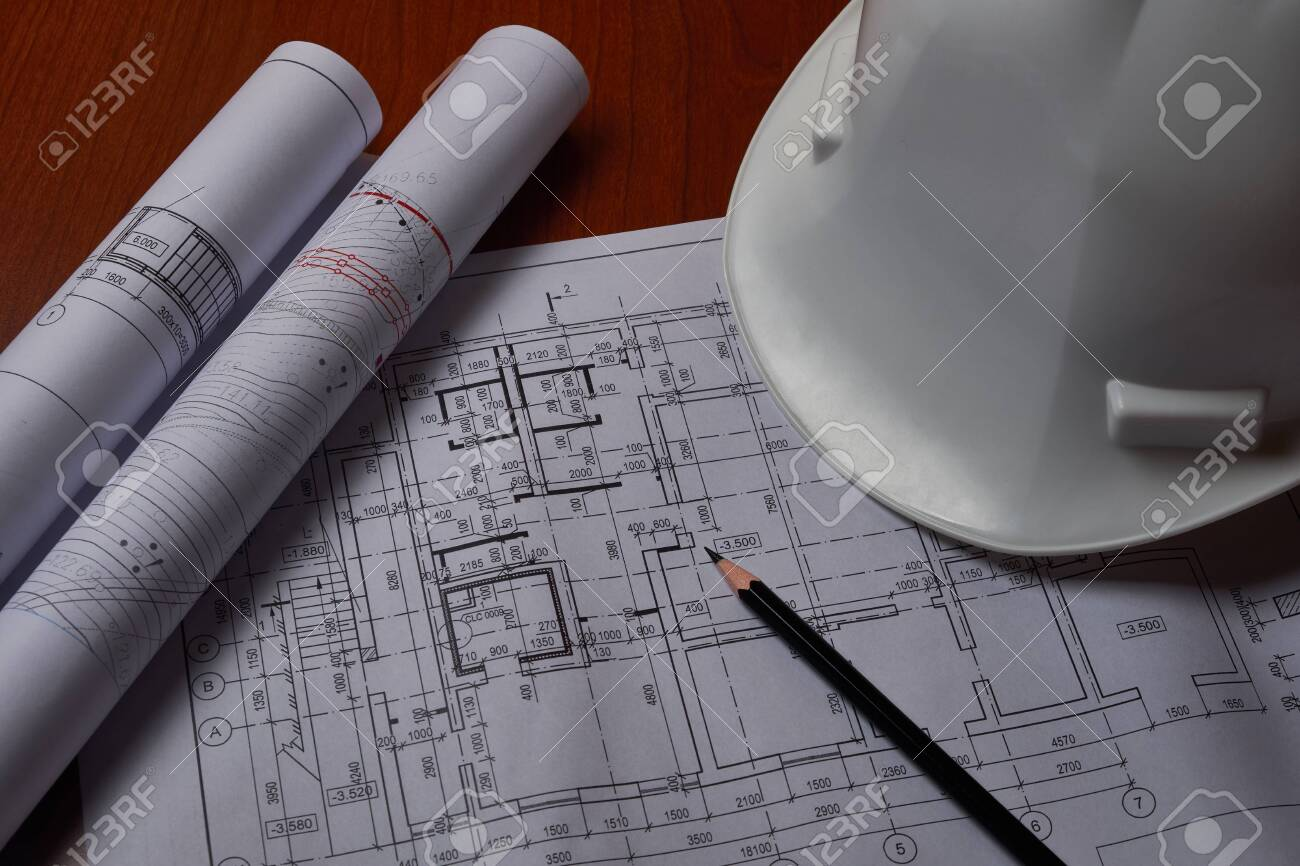 White hardhat and drawings at engineer workplace. - 144439586