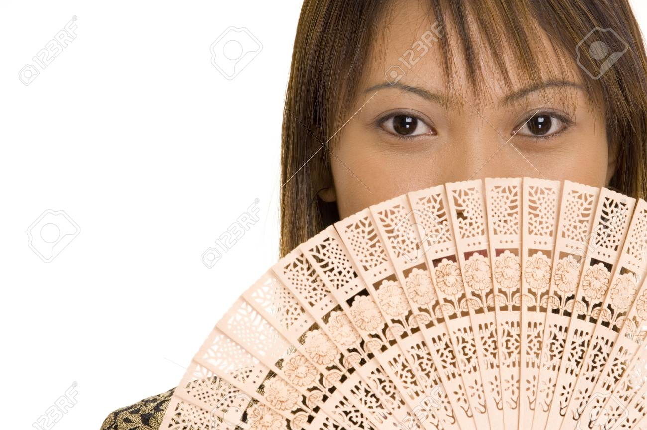 A pretty young asian girl holds a wooden fan in front of her mouth Stock Photo - 215462