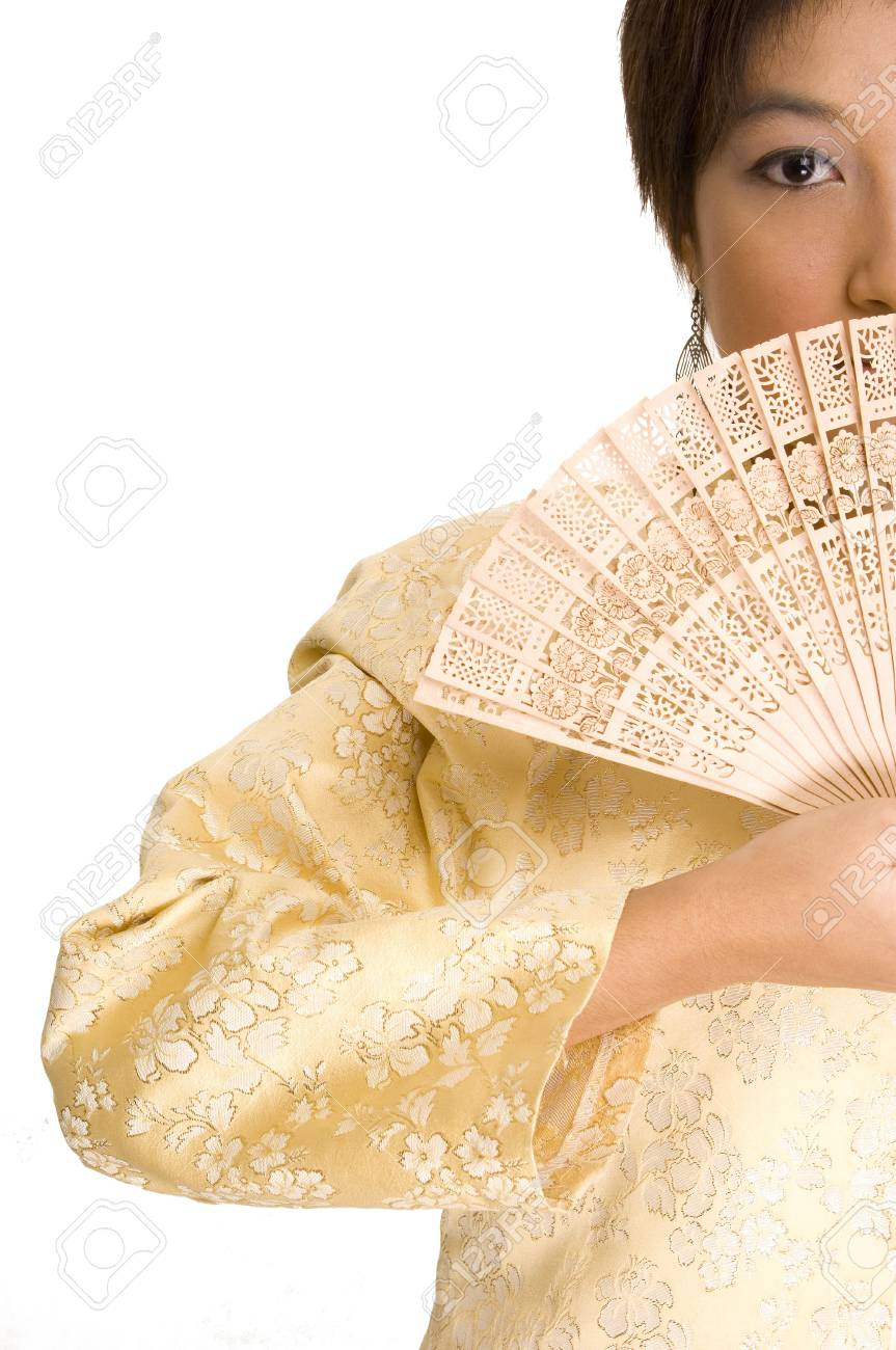 A pretty young asian girl wearing a yellow silk jacket hides her mouth with a wooden fan Stock Photo - 221057