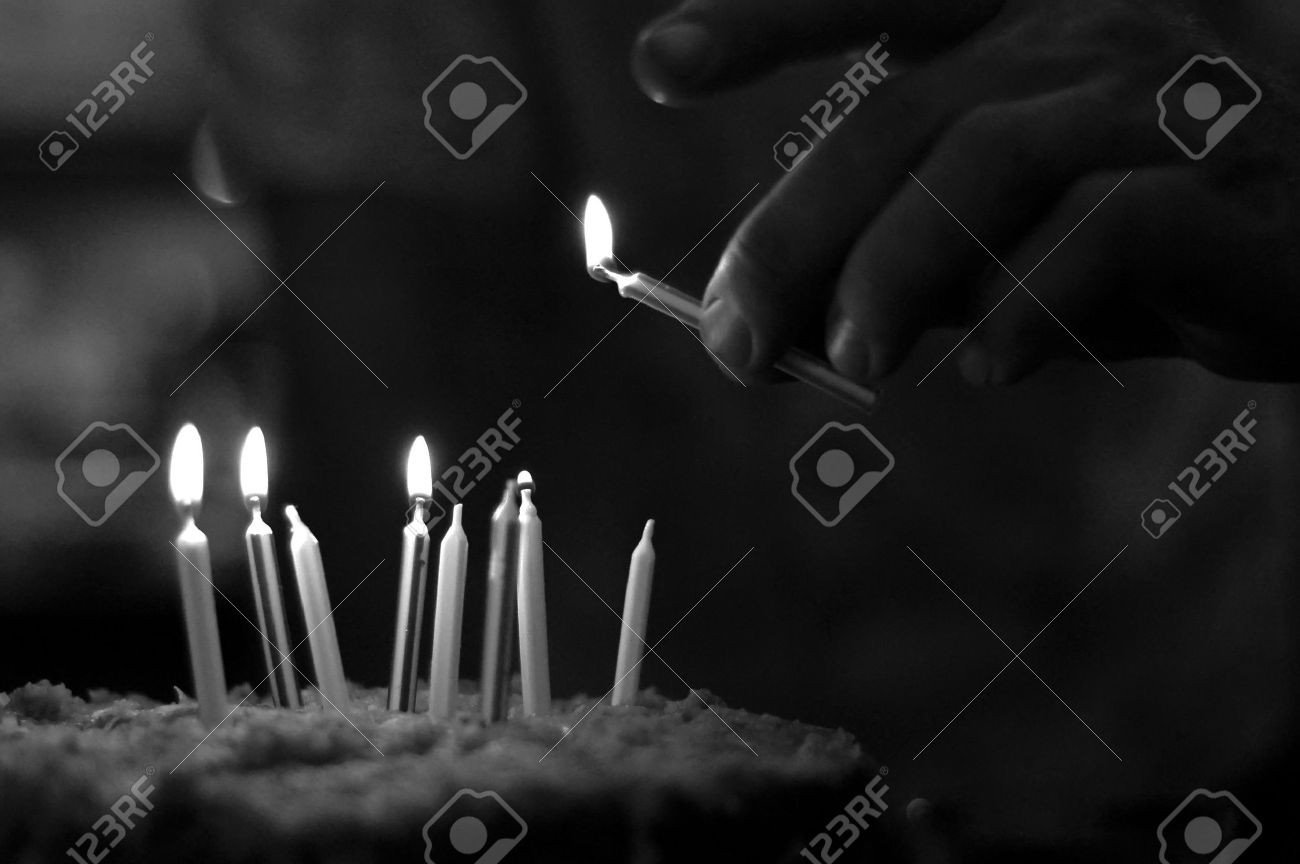 Man Lighting Candles On A Birthday Cake In Black And White Stock